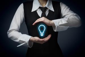 Ideenschutz durch Markenanmeldung - Managerin schütz mit ihren Händen eine Glühbirne - Symbolbild